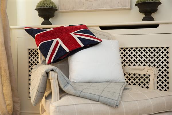 Back support cushion for sofa's. This image show the cushion on a chair in a beautiful setting wth a plant behind and a union jack cushion cover draped over the Sittingwell cushion highlighting that it is made in the UK.
