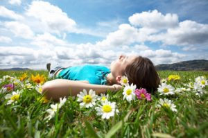 Image of beautiful sky with clouds and plants in the grass with someone lying on their back enjoying the sun for a blog about the health benefits of walking